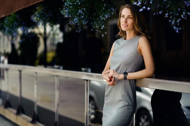 Jeune femme d'affaires en robe élégante à l'aide de smartwatches dans la rue
