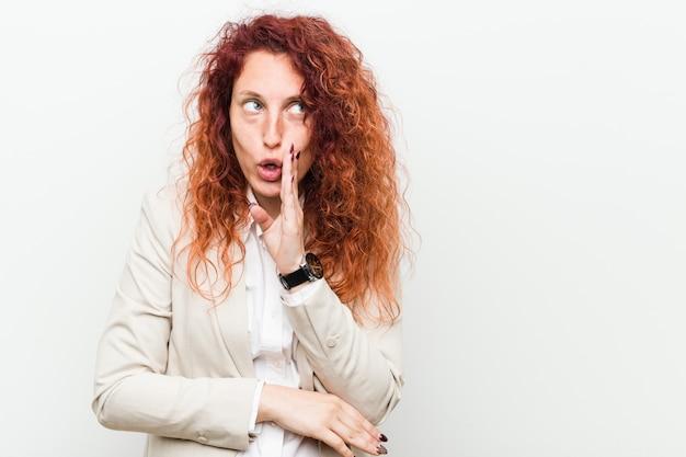 Jeune femme d'affaires de rousse naturelle isolée contre un mur blanc dit un secret secret concernant les nouvelles de freinage et regardant de côté