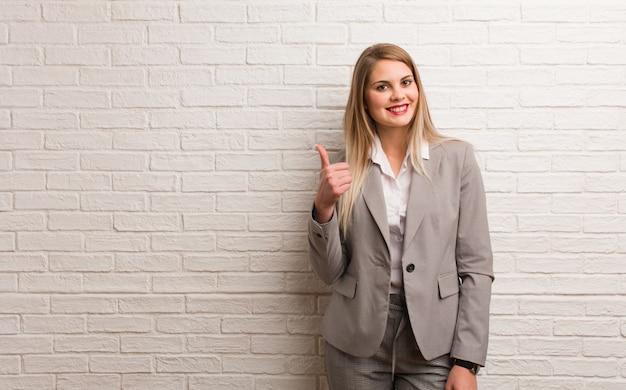Jeune femme d'affaires russe amusant et heureux de faire un geste de victoire