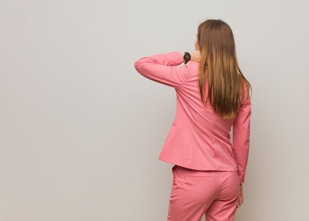 Jeune femme d'affaires russe par derrière penser à quelque chose