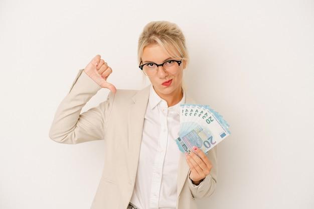 Jeune femme d'affaires russe tenant des billets isolés sur fond blanc se sent fière et confiante, exemple à suivre.