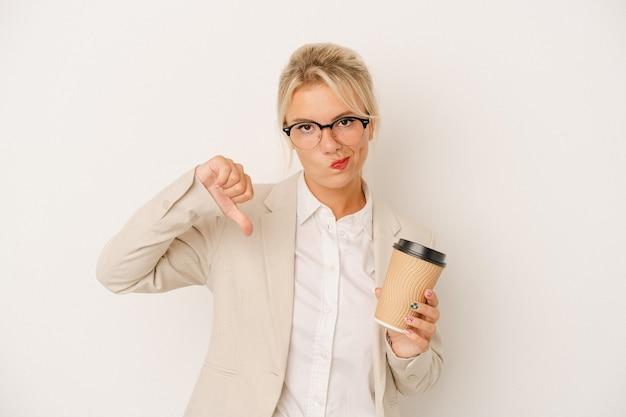 Jeune femme d'affaires russe tenant du café à emporter isolé sur fond blanc montrant un geste d'aversion, les pouces vers le bas. notion de désaccord.