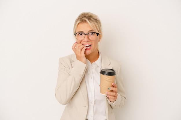 Jeune femme d'affaires russe tenant du café à emporter isolé sur fond blanc se ronger les ongles, nerveuse et très anxieuse.