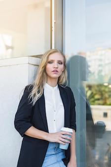 Jeune femme d'affaires s'appuyant sur le mur tenant la tasse de café à emporter