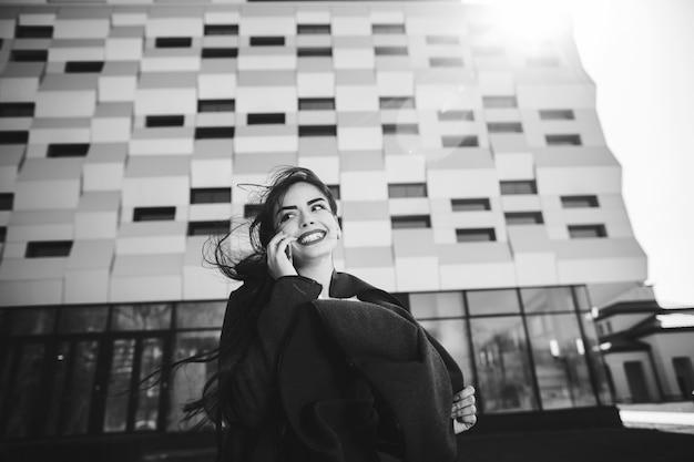 Jeune femme d'affaires s'exprimant au téléphone mobile pendant la pause café en plein air, près d'un immeuble de bureaux.