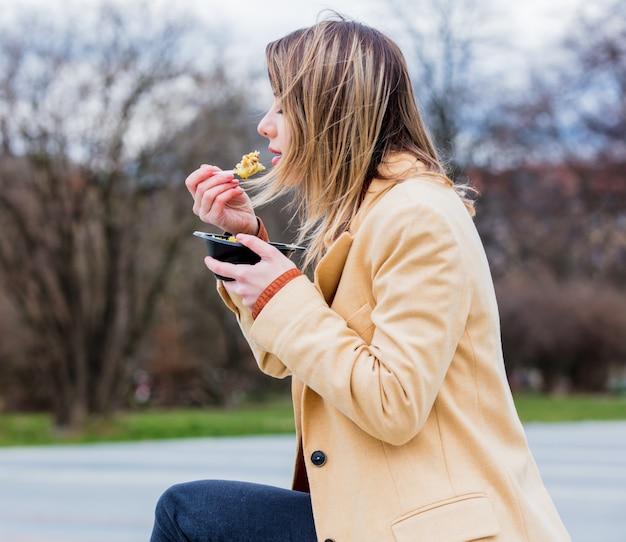 Jeune femme d'affaires avec une salade à la ville urbaine en plein air.