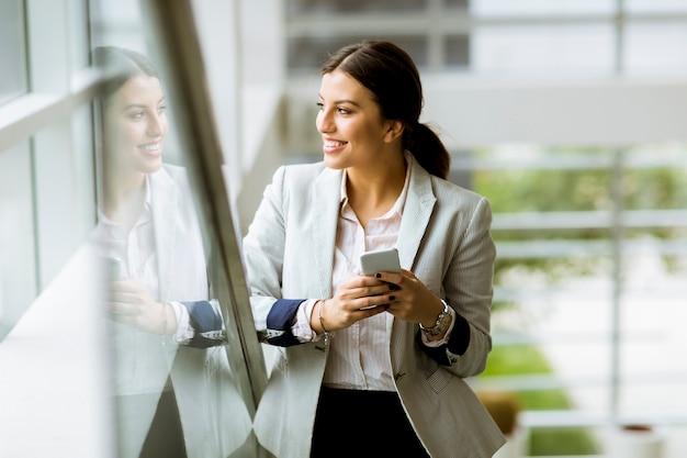 Jeune femme d'affaires se dresse sur les escaliers au bureau et utilise un téléphone mobile