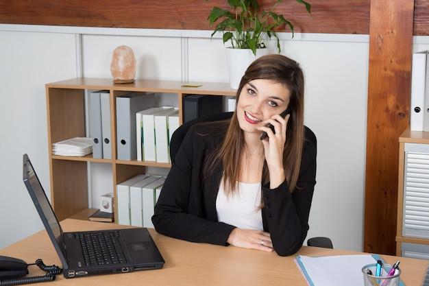 Jeune, femme affaires, séance, conversation, téléphone
