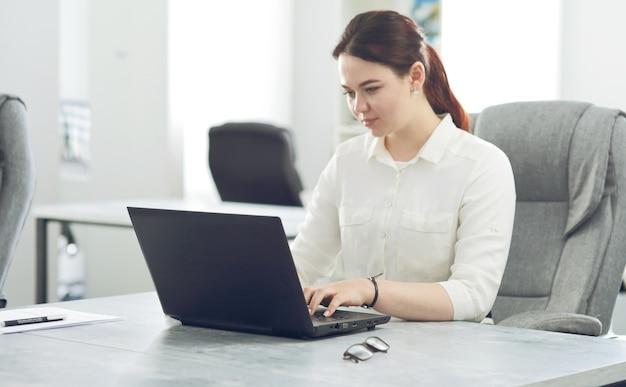 Jeune femme d'affaires séduisante travaillant au bureau souriant à la recherche d'un ordinateur portable.