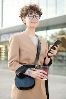 Jeune femme d'affaires sereine ou pensive avec une boisson et un sac à main faisant défiler les contacts ou envoyant des sms dans un smartphone en attendant le taxi