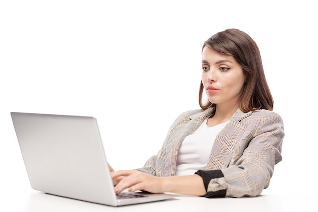 Jeune femme d'affaires sérieuse regardant l'écran de l'ordinateur portable tout en travaillant sur un projet ou un travail de planification