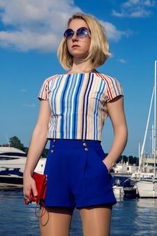 Jeune femme d'affaires en short bleu troncs debout et en attente d'une réunion à l'embarcadère avec yachts et bateaux