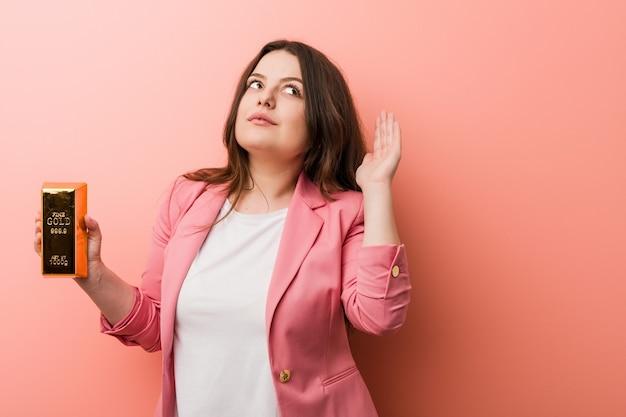 Jeune femme d'affaires sinueuse taille plus tenant un lingot d'or essayant d'écouter un potin.