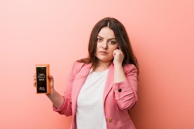 Jeune femme d'affaires sinueuse taille plus tenant un lingot d'or pointant sa tempe avec le doigt, pensant, concentrée sur une tâche.