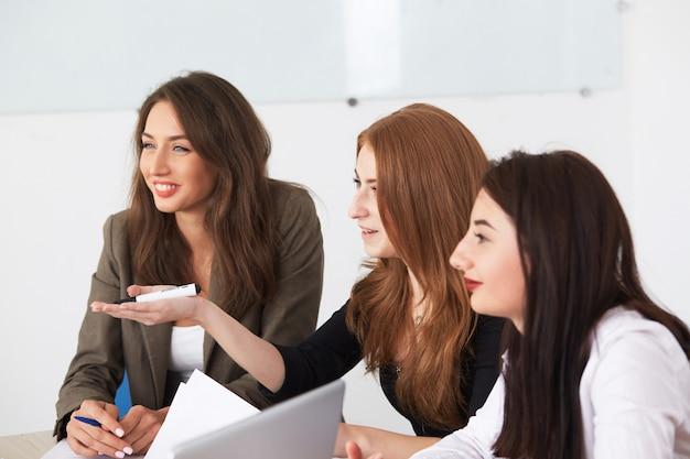 Jeune femme d'affaires souriant travaillant à un nouveau projet au bureau.