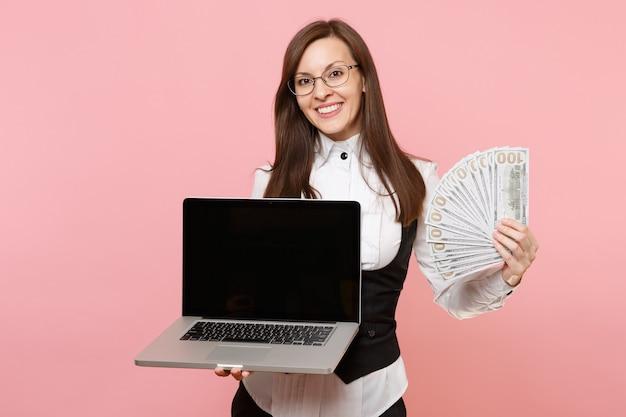 Jeune femme d'affaires souriante tenant un paquet de dollars, de l'argent en espèces et un ordinateur portable avec un écran vide isolé sur fond rose. dame patronne. réalisation carrière richesse. espace de copie.