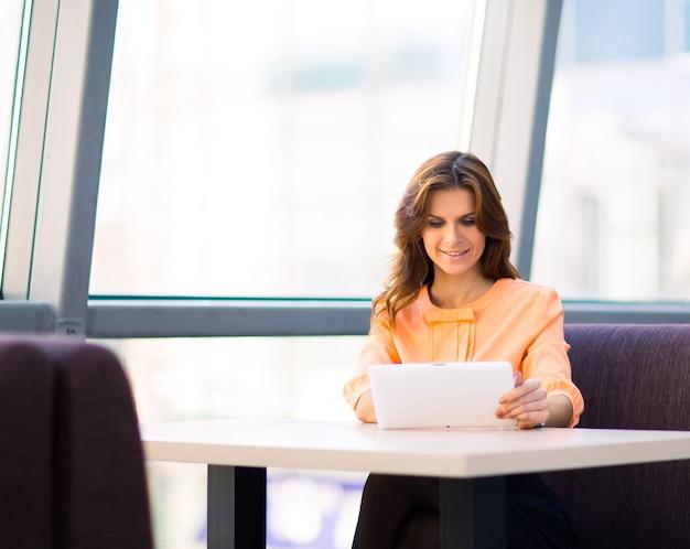 Jeune femme d'affaires souriante tenant une tablette numérique la table