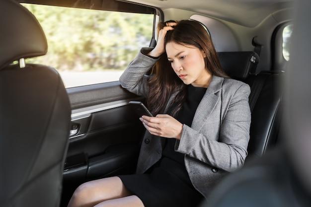 Jeune femme d'affaires stressée à l'aide d'un smartphone alors qu'elle était assise sur le siège arrière de la voiture
