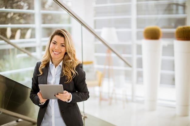Jeune femme d'affaires avec tablette dans le bureau moderne