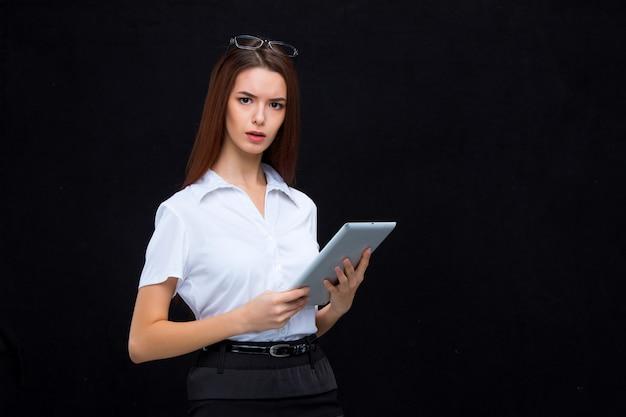 La jeune femme d'affaires avec tablette sur mur noir