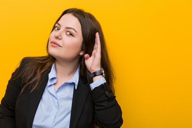 Jeune et femme d'affaires de taille plus caucasien essayant d'écouter un commérage.