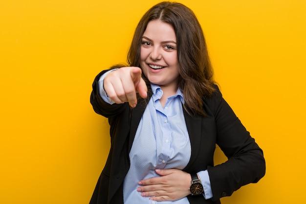 Jeune femme d'affaires de taille plus caucasien pointe avec le pouce loin, rire et insouciant.