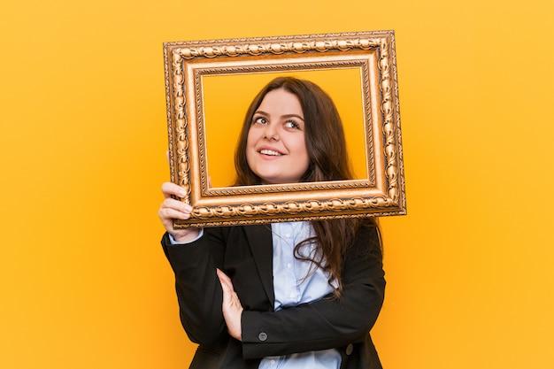 Jeune femme d'affaires de taille plus curvy tenant un cadre souriant confiant avec les bras croisés.