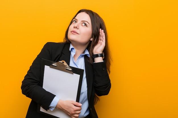 Jeune femme d'affaires de taille plus curvy tenant un presse-papiers en essayant d'écouter un commérage.