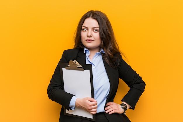 Jeune femme d'affaires de taille plus curvy tenant un presse-papiers souriant confiant avec les bras croisés.