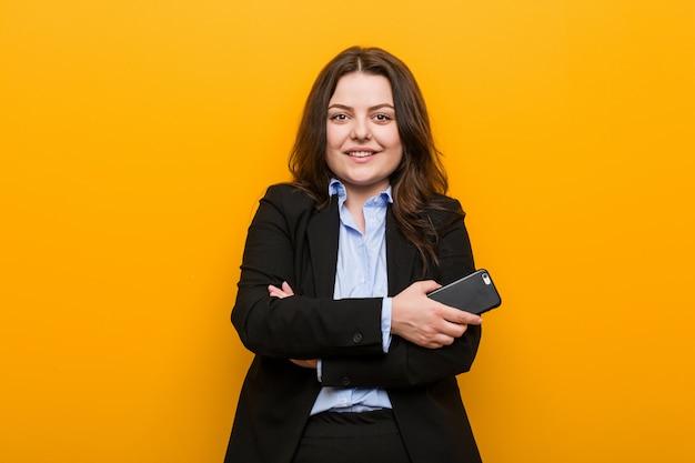 Jeune femme d'affaires de taille plus curvy tenant un téléphone souriant confiant avec les bras croisés.