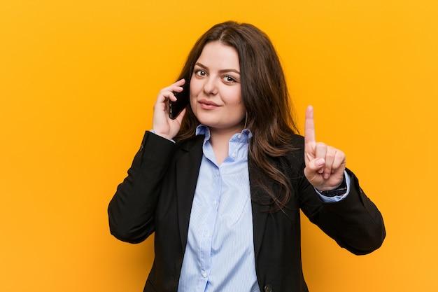 Jeune femme d'affaires de taille plus sinueuse tenant un téléphone montrant le numéro un avec le doigt.