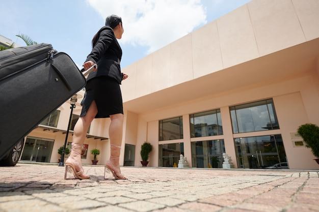 Jeune femme d'affaires en talons hauts tirant la valise en marchant jusqu'à l'entrée du bâtiment de l'hôtel