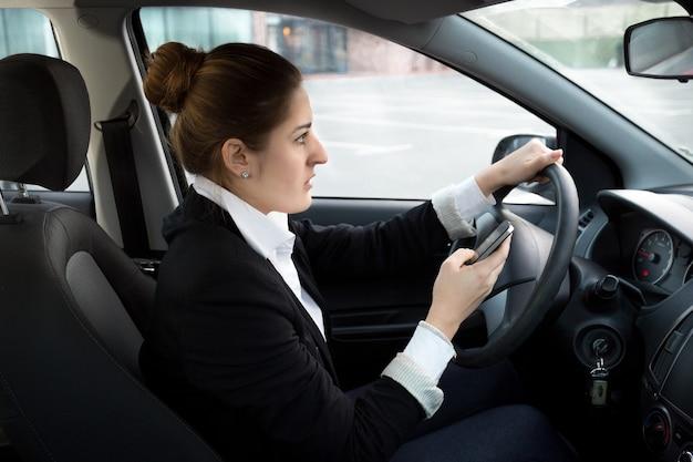 Jeune femme d'affaires tapant un message en conduisant une voiture