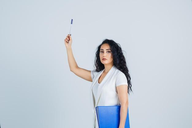 Jeune femme d'affaires tenant un dossier bleu
