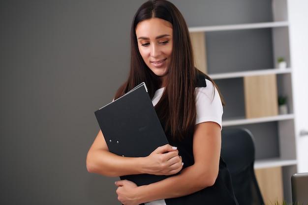Jeune femme d'affaires tenant un dossier noir assis au bureau