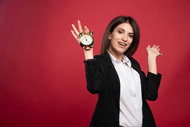 Jeune femme d'affaires tenant une horloge sur fond rouge.