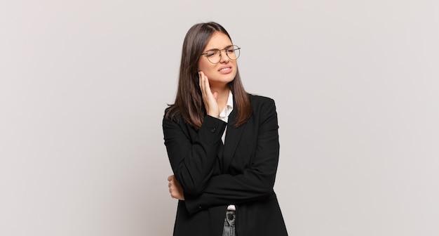 Jeune femme d'affaires tenant la joue et souffrant de maux de dents douloureux, se sentant malade, misérable et malheureux, à la recherche d'un dentiste