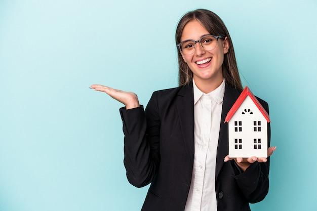Jeune femme d'affaires tenant une maison de jouets isolée sur fond bleu montrant un espace de copie sur une paume et tenant une autre main sur la taille.