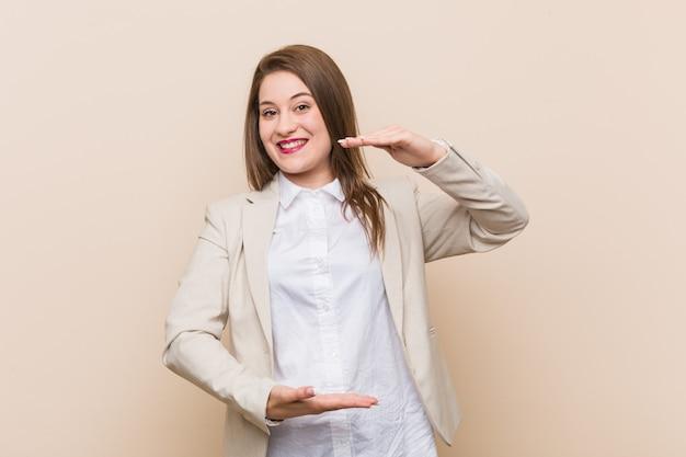 Jeune femme d'affaires tenant quelque chose à deux mains, présentation du produit.