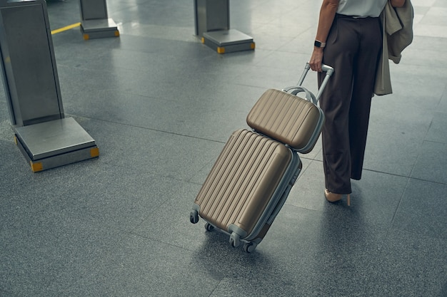 Jeune femme d'affaires tenant son manteau dans la main droite tout en étant seule à l'aéroport