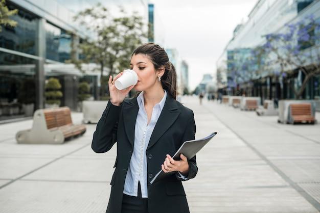 Jeune, femme affaires, tenue, dossier, main, boire, café, à, campus affaires