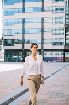 Jeune, femme affaires, tenue, ordinateur portable, main, marcher, sur, campus bureau