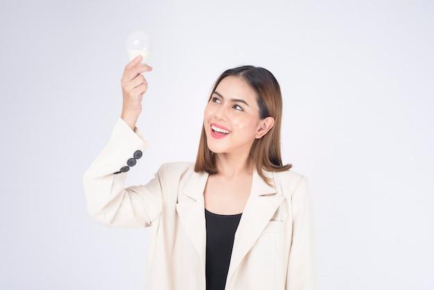Une jeune femme d'affaires tient une ampoule portant un costume sur fond blanc studio