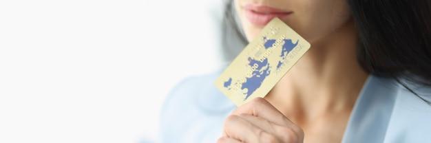 La jeune femme d'affaires tient le plan rapproché de carte bancaire en plastique