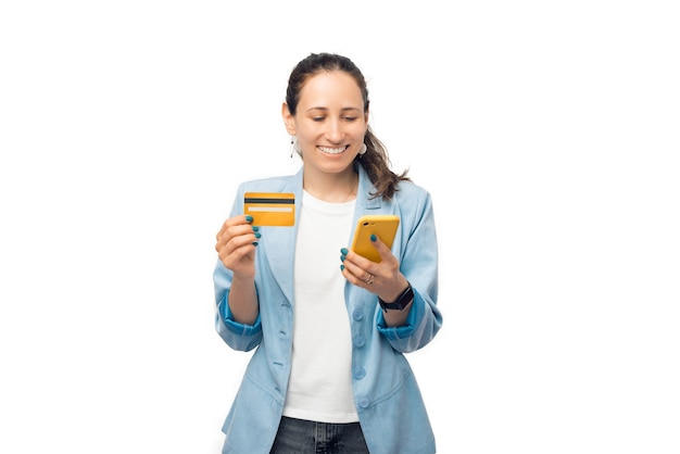 Une jeune femme d'affaires tient sa carte de crédit et son téléphone en utilisant les services bancaires mobiles.