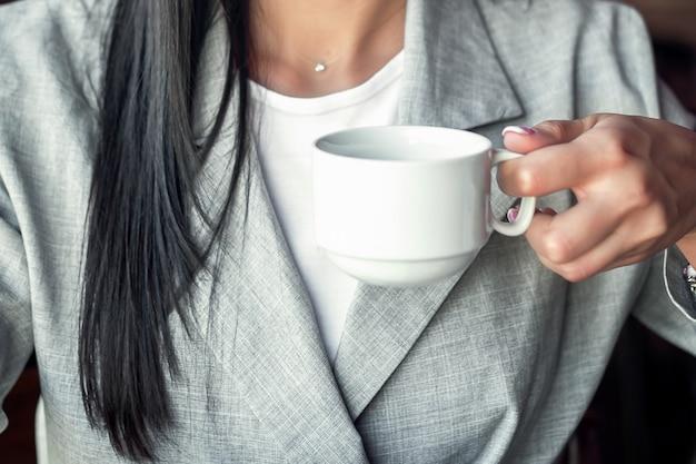 Jeune femme d'affaires tient une tasse blanche de boisson chaude portant une veste, gros plan.