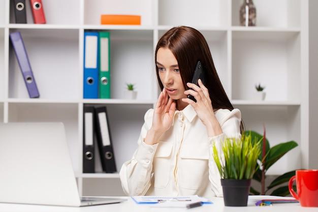Jeune femme d'affaires travaillant dans son bureau sur ordinateur portable