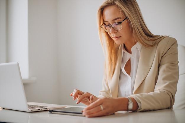 Jeune femme d'affaires travaillant sur ordinateur au bureau