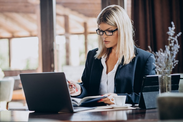 Jeune femme d'affaires travaillant sur ordinateur dans un café