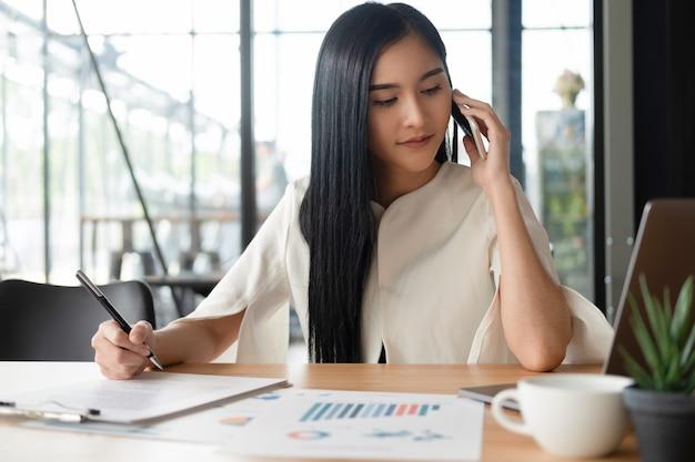 Jeune femme d'affaires travaillant avec un ordinateur portable mobile et des documents au bureau, concept d'entreprise